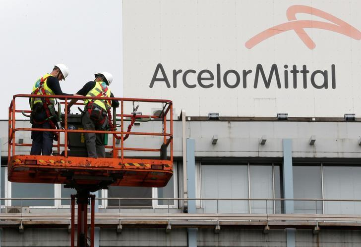 Workers stand near the logo of ArcelorMittal, the world's largest producer of steel, at the steel plant in Ghent, Belgium, July 7, 2016. REUTERS/Francois Lenoir