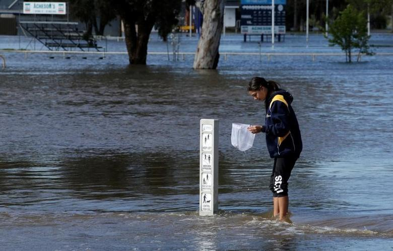 Local resident Nadia Hartwig fishes with a net while standing on a flooded jogging path in the overflowing Forbes Lake after heavy rain created a declared natural disaster zone in the midwestern New South Wales town of Forbes, Australia, September 27, 2016.   REUTERS/Jason Reed