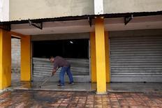 Doce personas murieron la madrugada del viernes en zonas populares de Caracas, la mayoría electrocutadas, durante una nueva jornada de protestas antigubernamentales que derivó en saqueos, dijo el Ministerio Público venezolano. En la imagen, un hombre limpia junto a la puerta destrozada de un supermercado que fue saqueado en Caracas el 21 de abril. REUTERS/Carlos Garcia Rawlins