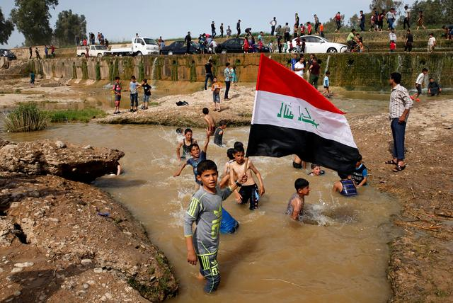 A boy holds the Iraqi flag as he plays in the water with other children during a Friday holiday at Shallalat district (Arabic for ''waterfalls'') in eastern Mosul, Iraq, April 21, 2017. REUTERS/Muhammad Hamed