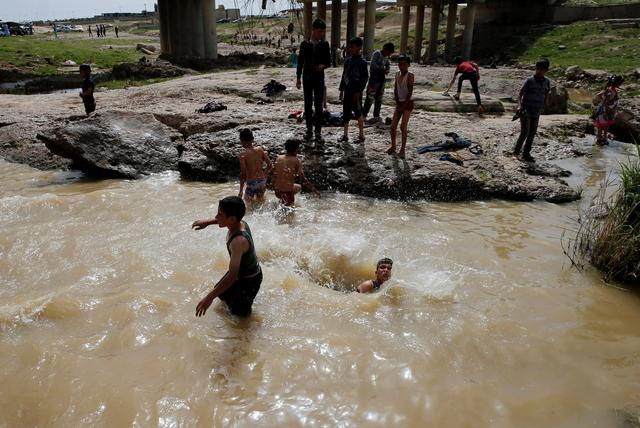 Iraqi youths swim as they enjoy their Friday holiday at Shallalat district (Arabic for ''waterfalls'') in eastern Mosul, Iraq, April 21, 2017. REUTERS/ Muhammad Hamed
