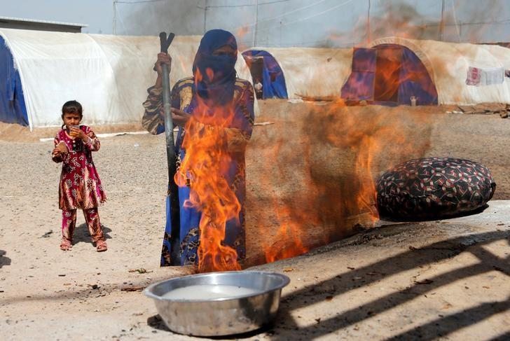 A displaced woman who fled the Islamic State stronghold of Mosul lights a fire to make bread with her children at Khazer camp, Iraq April 21, 2017. REUTERS/Muhammad Hamed