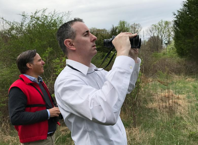 U.S. Rep. Brian Fitzpatrick (R-PA), with Greg Goldman (L), executive director of Audubon Pennsylvania, tries to spot a red-winged blackbird while on a birdwatching tour hosted by the Audubon Pennsylvania in New Hope, Pennsylvania, U.S., April 22, 2017.  REUTERS/Emily Flitter