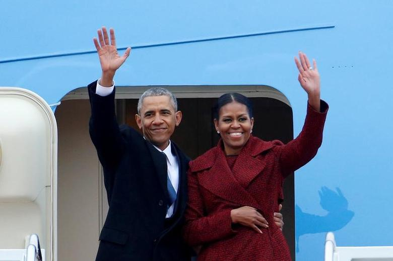 Former president Barack Obama waves with his wife Michelle as they board Special Air Mission 28000, a Boeing 747 which serves as Air Force One, at Joint Base Andrews, Maryland, U.S. on January 20, 2017.   REUTERS/Brendan McDermid/Files