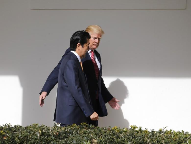 Japanese Prime Minister Shinzo Abe and U.S. President Donald Trump (R) walk along the colonnade after their Oval Office meeting and before holding a joint news conference at the White House in Washington, U.S., February 10, 2017.   REUTERS/Jim Bourg