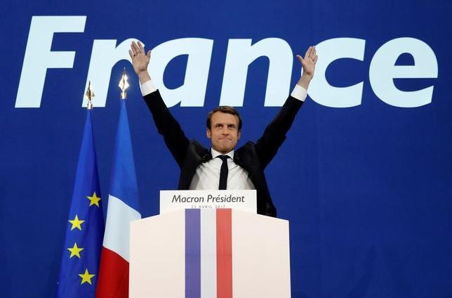 4月23日、フランス大統領選の第1回投票で、中道系独立候補のエマニュエル・マクロン前経済相は2週間後の決選投票への進出を決めた。しかし、大統領として改革を実行するためには決選投票を大差で制し、6月の国民議会(下院)選挙に向けた基盤を固めることが重要になる。写真は決選投票への進出を祝うマクロン前経済相。パリで23日撮影(2017年 ロイター/Benoit Tessier)