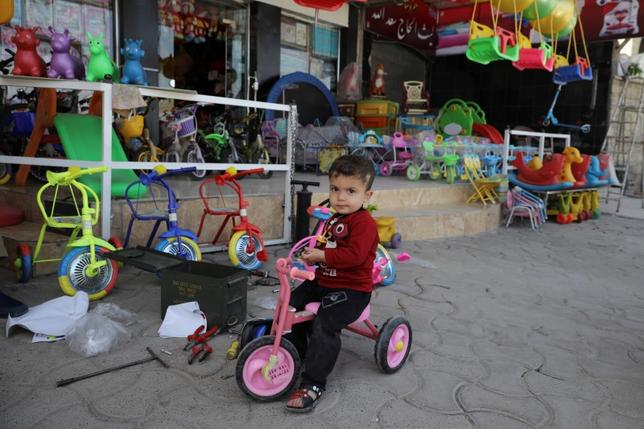 A boy sits on his bicycle in front of a toy store, in eastern Mosul, Iraq April 21, 2017. REUTERS/Marko Djurica