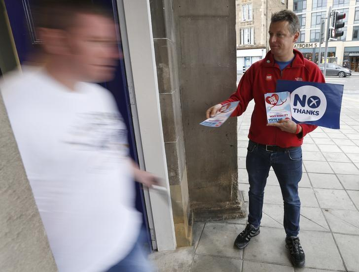 File photo: A 'No' campaigner hands out leaflets to commuters as they arrive at Edinburgh's Haymarket station, in Scotland September 17, 2014.         REUTERS/Russell Cheyne