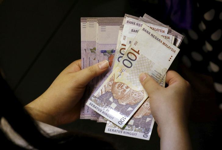 A customer counts her ringgit notes outside a money changer at the central business district in Singapore August 25, 2015.  REUTERS/Edgar Su/File Photo
