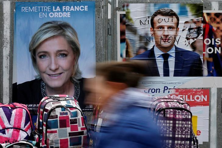 A woman walks past official posters of candidates for the 2017 French presidential election Marine Le Pen, French National Front (FN) political party leader (L) and Emmanuel Macron, head of the political movement En Marche !, or Onwards !, (R) on a local market in Bethune, France April 24, 2017. REUTERS/Pascal Rossignol/Files