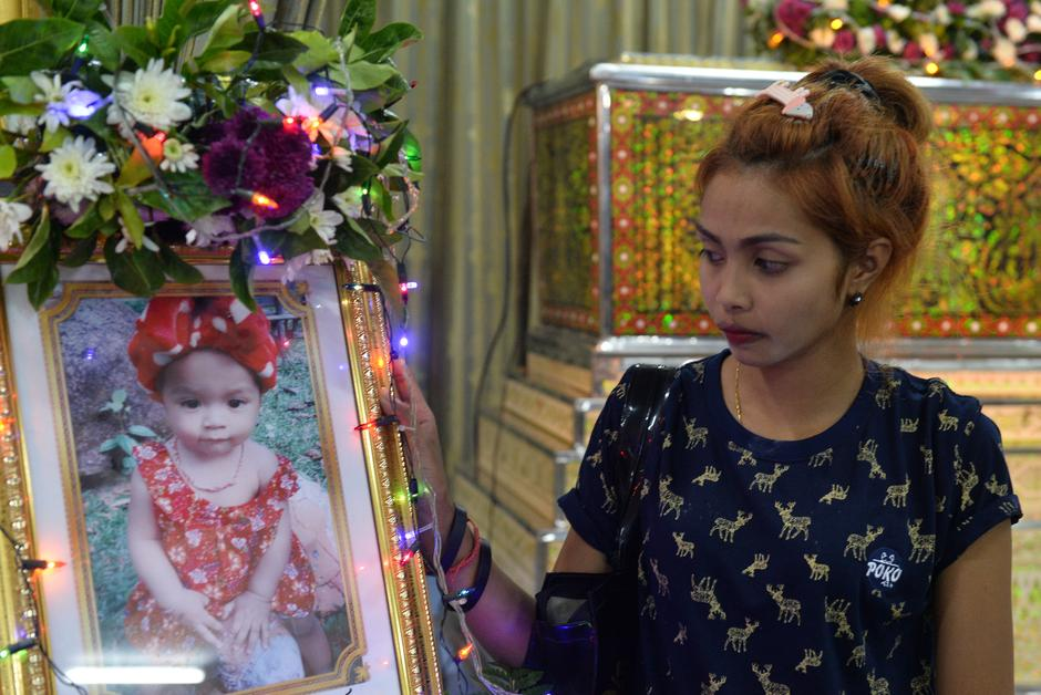 ... daughter who was killed by her father who broadcast the murder on  Facebook, stands next to a picture of her daughter at a temple in Phuket,  Thailand ...