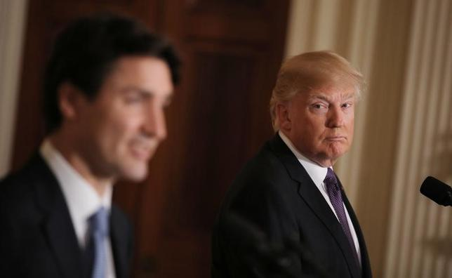 4月25日、米商務省はカナダ産針葉樹材の輸入に平均20%の相殺関税を適用する。写真右はトランプ米大統領。ワシントンで2月撮影(2017年 ロイター/Carlos Barria)