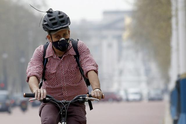 A cyclist wears a mask as he cycles near Buckingham Palace in London April 2, 2014.     REUTERS/Luke MacGregor
