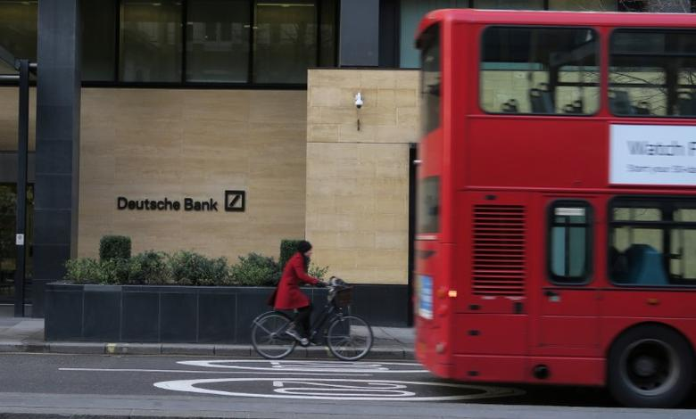 FILE PHOTO: A woman cycles behind a London bus as they pass by a Deutsche Bank building in the City of London March 30, 2016.  REUTERS/Russell Boyce/File Photo -