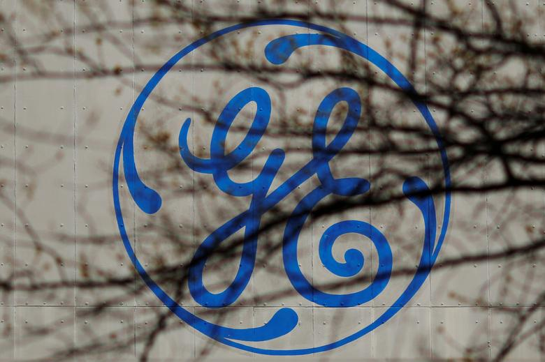 FILE PHOTO: The logo of a General Electric (GE) facility is seen behind tree branches in Medford, Massachusetts, U.S., April 20, 2017.   REUTERS/Brian Snyder/File Photo