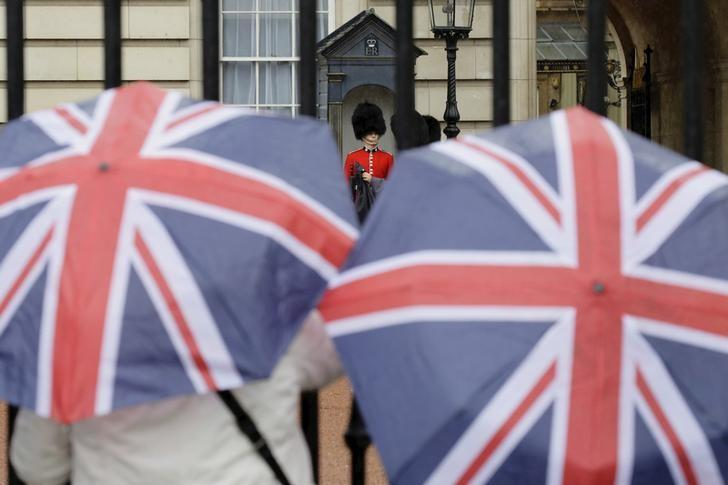 Tourists stand in the rain outside Buckingham Palace in London, Britain August 31, 2015. REUTERS/Kevin Coombs