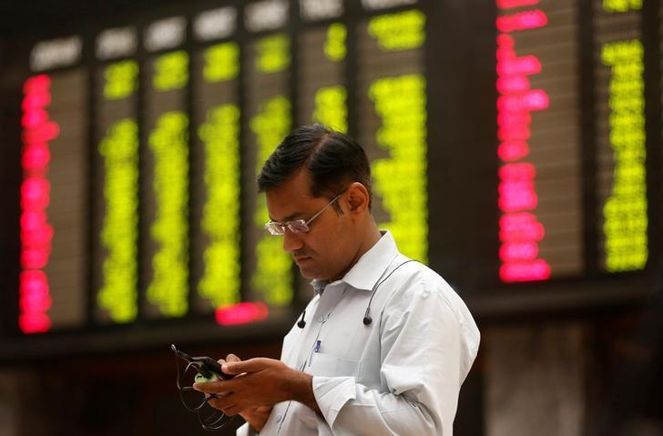 A man uses his cell phone as he stands in front of display board showing stock prices during a trading session in the halls of Pakistan Stock Exchange (PSE) Karachi, Pakistan April 19, 2017. REUTERS/Akhtar Soomro