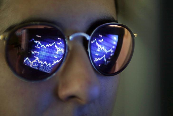 A computer screen showing stock graphs is reflected on glasses in this illustration photo taken in Bordeaux, France, March 30, 2016. REUTERS/Regis Duvignau