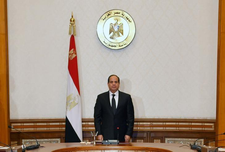 FILE PHOTO: Egyptian President Abdel Fattah al-Sisi stands and observes a minute of silence for the victims of two separate church attacks during Palm Sunday prayers, with leaders of the Supreme Council of the Armed Forces and the Supreme Council for Police to discuss developments in the security situation in Egypt, as well as developments in the country's fight against terrorism, at the Ittihadiya presidential palace in Cairo, Egypt, April 9, 2017, in this handout picture courtesy of the Egyptian Presidency. The Egyptian Presidency/Handout via REUTERS