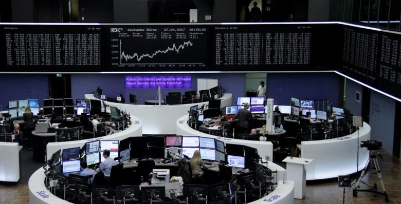 Traders work at their desks in front of the German share price index, DAX board, at the stock exchange in Frankfurt, Germany, April 27, 2017. REUTERS/Staff/Remote