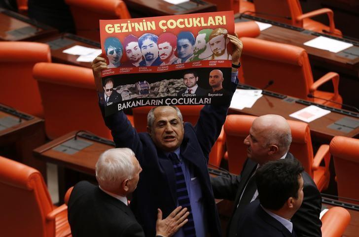 Republican People's Party (CHP) lawmaker Musa Cam holds a banner during a debate at the parliament on draft budget in Ankara December 20, 2013. REUTERS/Umit Bektas/Files