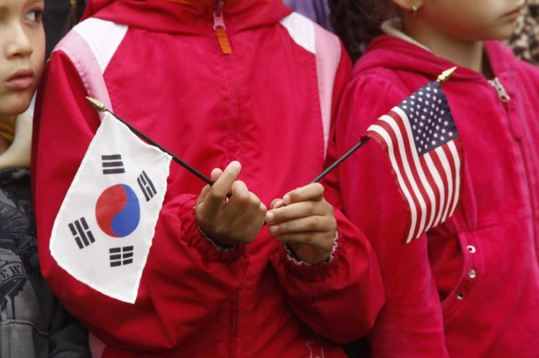 FILE PHOTO: A child holds U.S. and South Korean flags prior to the state arrival of South Korean President Lee Myung-bak at the White House in Washington, October 13, 2011. REUTERS/Kevin Lamarque