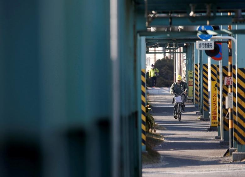 FILE PHOTO: A worker cycles near a factory at the Keihin industrial zone in Kawasaki, Japan February 28, 2017. REUTERS/Issei Kato/File Photo