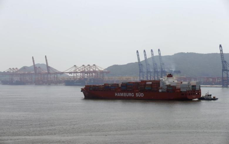 A Hamburg Sud ship carrying containers arrives as the Hyundai Merchant Marine container terminal is seen in the background at the Busan New Port in Busan, about 420 km (261 miles) southeast of Seoul, August 8, 2013.  REUTERS/Lee Jae-Won