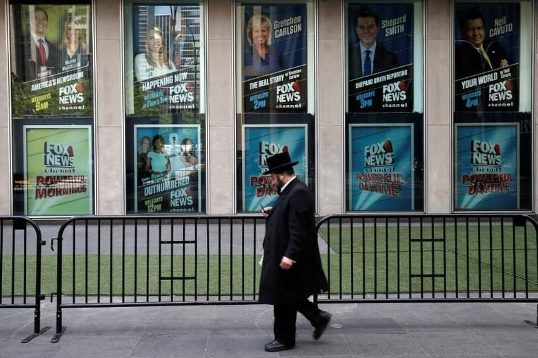 A man walks past posters of Fox News personalities including Gretchen Carlson, (C-top) who was recently fired from Fox News and who has filed a sexual harassment lawsuit against Fox News Chairman and CEO Roger Ailes, at the News Corporation headquarters building in Manhattan, New York, U.S., July 6, 2016. REUTERS/Mike Segar