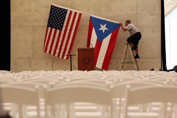 A worker takes off U.S and Puerto Rican flag after rally of U.S. Democratic presidential candidate Bernie Sanders in San Juan, Puerto Rico, May 16, 2016. REUTERS/Alvin Baez