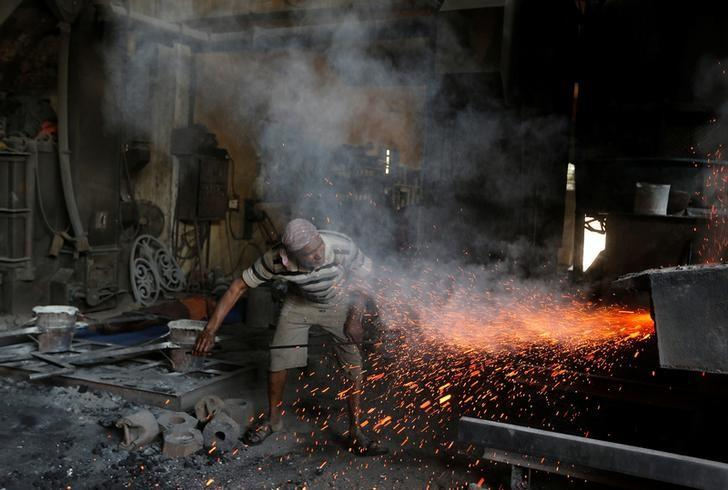 A worker clears a furnace at an iron casting factory in Ahmedabad, India March 1, 2017. REUTERS/Amit Dave/Files