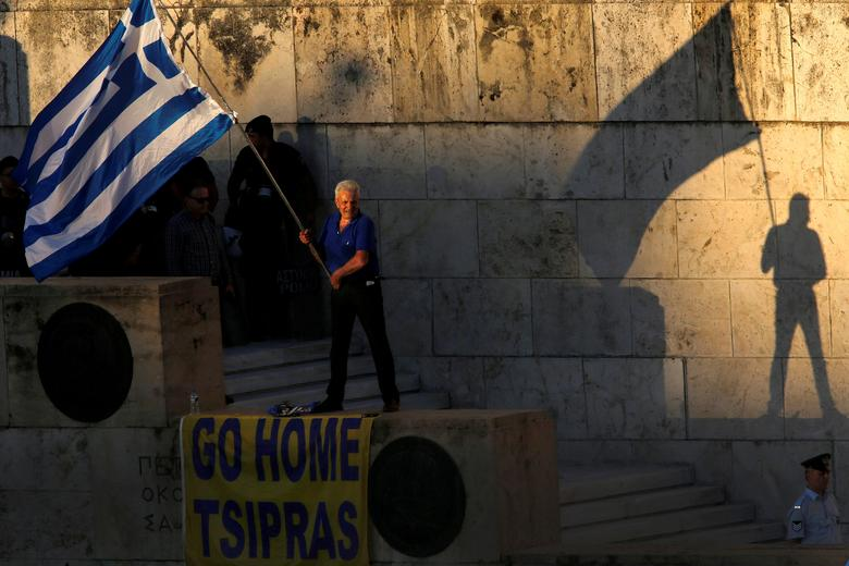 FILE PHOTO: An anti-government demonstrator waves a Greek flag outside the parliament during a protest in Athens, Greece June 15, 2016. REUTERS/Yannis Behrakis/File Photo