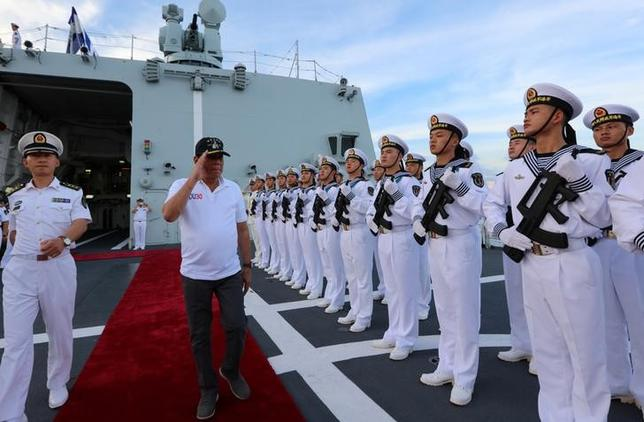 Philippine President Rodrigo Duterte salutes Chinese People's Liberation Army (PLA) navy soldiers during a visit to a Chinese Naval ship in Davao city, Philippines, May 1, 2017. Picture taken May 1, 2017. China Daily/via REUTERS