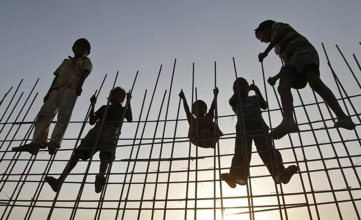 Children of labourers are silhouetted against the setting sun at the construction site of a residential complex in Ahmedabad April 20, 2011. REUTERS/Amit Dave/Files
