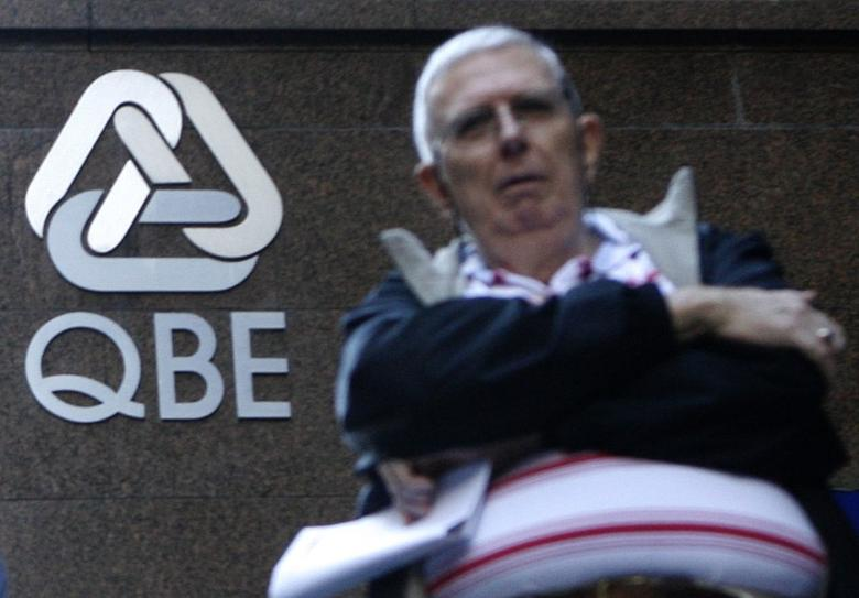 FILE PHOTO: A man waits in front of a QBE Insurance Group headquarters in central Sydney May 19, 2008. REUTERS/Daniel Munoz