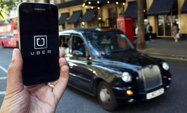 A photo illustration shows the Uber app logo displayed on a mobile telephone, as it is held up for a posed photograph in central London, Britain August 17, 2016. REUTERS/Neil Hall/Illustration/Files