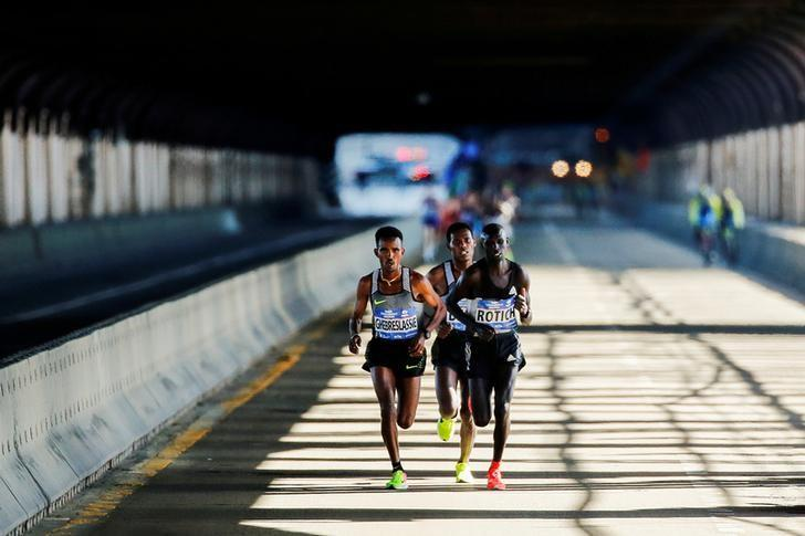 Ghirmay Ghebreslassie (L) of Eritrea leads the men's pack next to Hosea Rotich of Kenya and Lelisa Desisa of Ethiopia as they cross the Ed Koch Queensboro Bridge during the 2016 New York City Marathon in New York City, U.S. November 6, 2016.  REUTERS/Eduardo Munoz/Files
