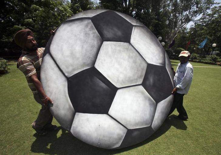 REPRESENTATIVE IMAGE: Labourers carry a plywood cut-out of a soccer ball for installation at a hotel in Chandigarh June 12, 2010. REUTERS/Ajay Verma/Files