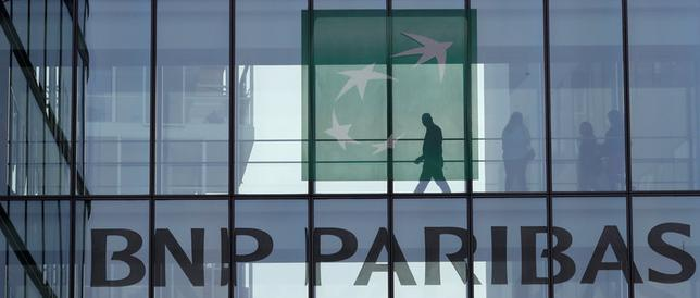 FILE PHOTO: A man is seen in silhouette as he walks behind the logo of BNP Paribas in a building in Issy-les-Moulineaux, near Paris, France, April 5, 2017. REUTERS/Gonzalo Fuentes