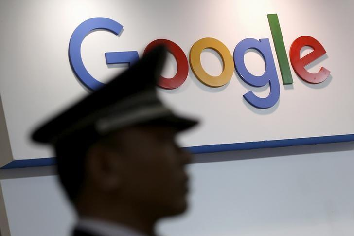 A security guard keeps watch as he walks past a logo of Google in Shanghai, China, April 21, 2016. REUTERS/Aly Song/File Photo