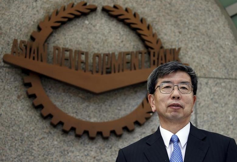 Asian Development Bank (ADB) President Takehiko Nakao poses in front of the logo of ADB at its headquarters in Mandaluyong, Metro Manila after a forum with members of the Foreign Correspondents Association of the Philippines January 8, 2016.  REUTERS/Erik De Castro