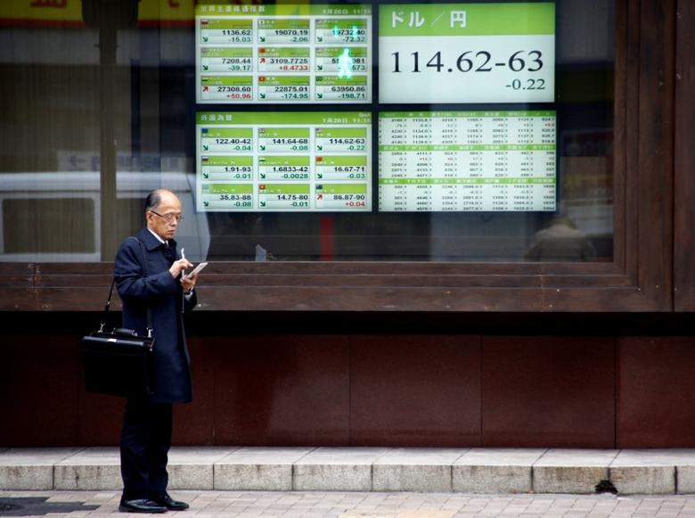 FILE PHOTO-A man stands in front of electronic boards showing stock prices and exchange rate between Japanese Yen and U.S dollar outside a brokerage in Tokyo, Japan, January 20, 2017.  REUTERS/Kim Kyung-Hoon /File Photo