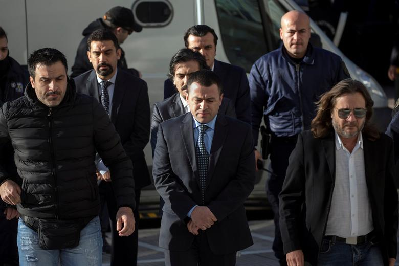 FILE PHOTO - Four of the eight Turkish soldiers (C), who fled to Greece in a helicopter and requested political asylum after a failed military coup against the government, line up as they are escorted by police officers at the Supreme Court in Athens, Greece, January 13, 2017. REUTERS/Alkis Konstantinidis/File Photo