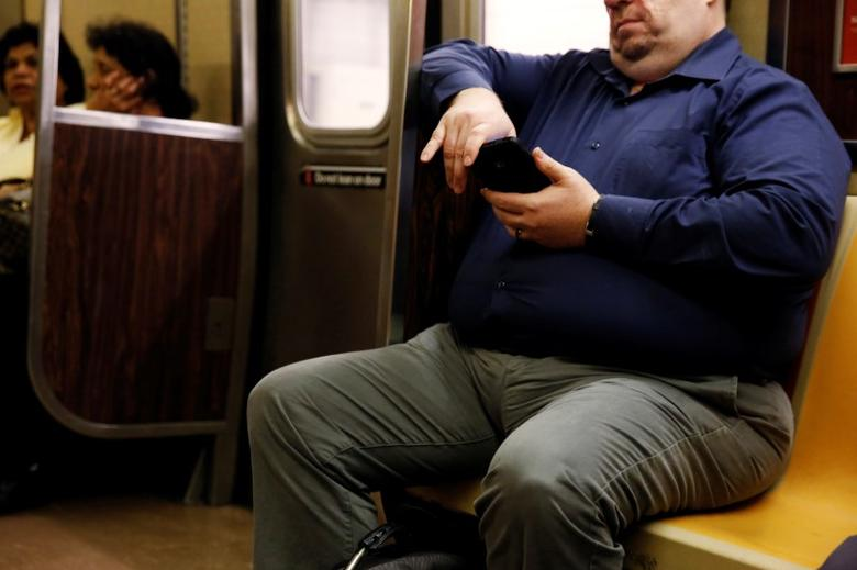 A man uses his phone while riding the subway in New York, U.S., August 24, 2016. Picture taken August 24, 2016. REUTERS/Lucas Jackson/Files