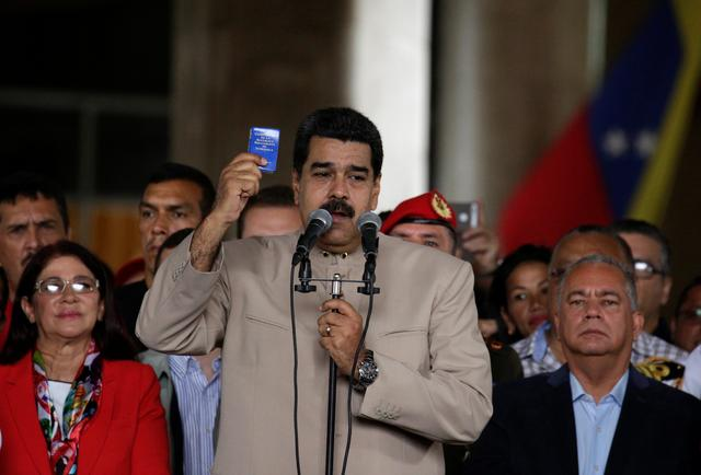 Venezuela's President Nicolas Maduro holds a copy of the Venezuelan constitution as he speaks during a gathering outside the National Electoral Council (CNE) where he presented his proposal to set up a National Constituent Assembly, in Caracas, Venezuela May 3, 2017. REUTERS/Marco Bello