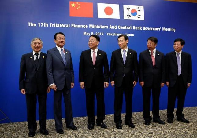 5月5日、日中韓の3カ国は横浜市で開かれているアジア開発銀行(ADB)の年次総会に合わせて開催した財務相・中央銀行総裁会議で、保護主義への対抗を柱とした共同声明を採択した。写真は黒田東彦日銀総裁(一番左)麻生太郎財務相(左から2番目)など会議の参加者。横浜で撮影(2017年 ロイター/Issei Kato)