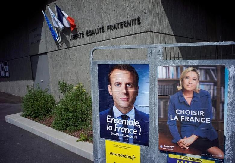 FILE PHOTO: New official posters for the candidates for the 2017 French presidential election, Emmanuel Macron (L), head of the political movement En Marche !, or Onwards !, and Marine Le Pen (R), French National Front (FN) political party leader, are displayed in Fontaines-sur-Saone, near Lyon, France, April 30, 2017. REUTERS/Robert Pratta/File Photo