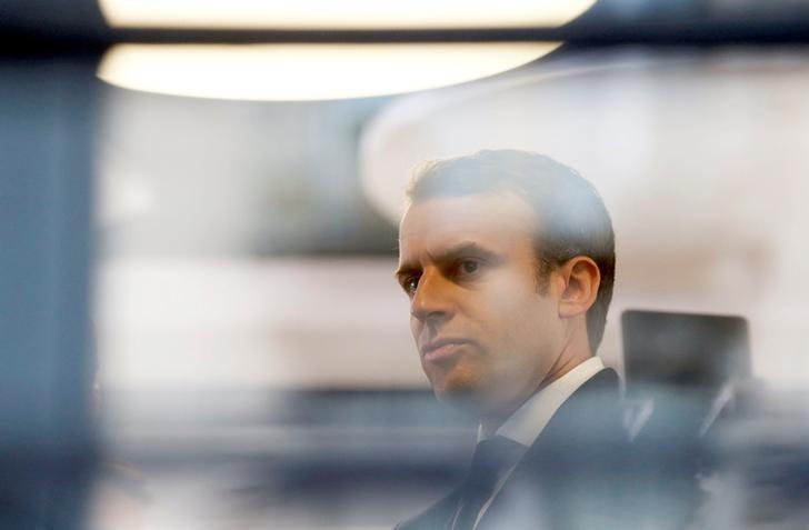 Emmanuel Macron, head of the political movement En Marche !, or Onwards !, and candidate for the 2017 presidential election, is pictured through a window of his hotel during a campaign visit in Rodez, France, May 5, 2017. REUTERS/Regis Duvignau/Files