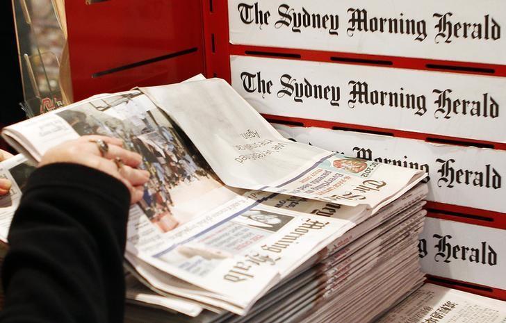 A woman picks up a copy of the Sydney Morning Herald newspaper, a Fairfax Media publication, in Sydney June 18, 2012. REUTERS/Daniel Munoz