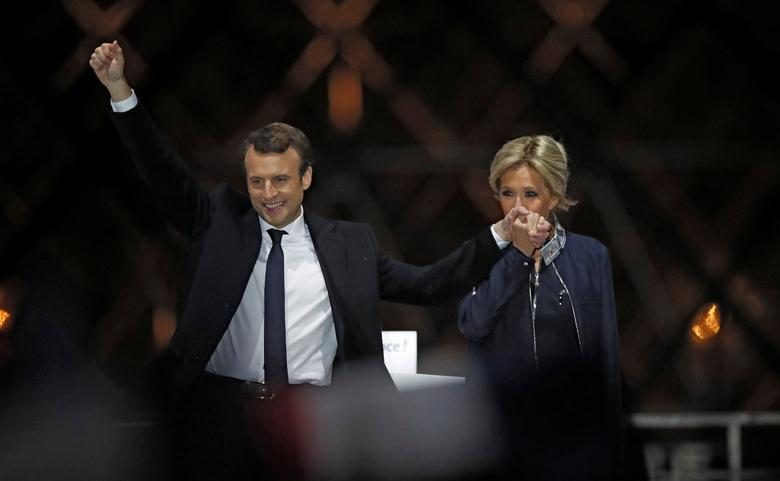 French President elect Emmanuel Macron and his wife Brigitte Trogneux celebrate on the stage at his victory rally near the Louvre in Paris, France May 7, 2017. REUTERS/Christian Hartmann